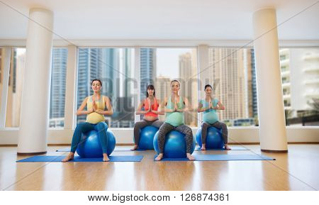pregnancy, sport, fitness, people and healthy lifestyle concept - group of happy pregnant women exercising on ball in gym over city window view background