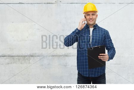 repair, building, construction, business and maintenance concept - smiling man or builder in helmet with clipboard calling on smartphone over gray concrete wall background