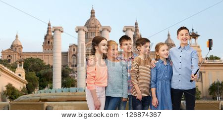 childhood, travel, tourism, technology and people concept - happy children talking picture by smartphone on selfie stick ovetrnational museum of barcelona background