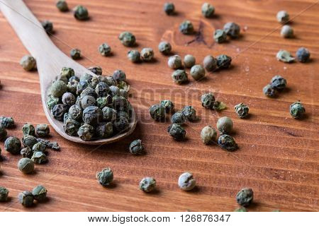 Green Peppercorn Seeds On Wooden Table