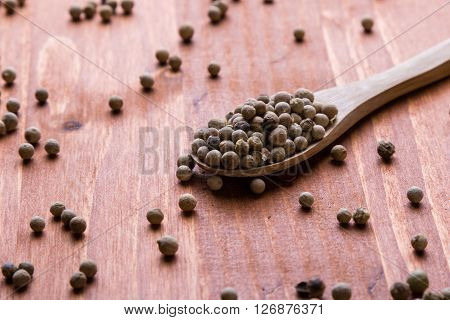 White Peppercorn Seeds On Wooden Table