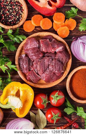 Ingredients for goulash or stew cooking: raw meatherbsspicesvegetables on dark wooden background top view.
