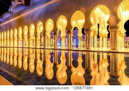 Abu Dhabi, UAE- March 2, 2016:Beautiful walkway illuminated at night in Abu Dhabi Sheikh Zayed Grand Mosque UAE