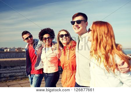 tourism, travel, people and leisure concept - group of happy teenage friends walking along city street and talking
