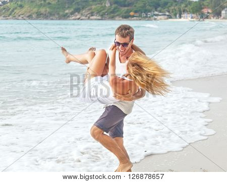 Happy Young Man Holding His Girlfriend In His Arms. Against The Background Of The Sea