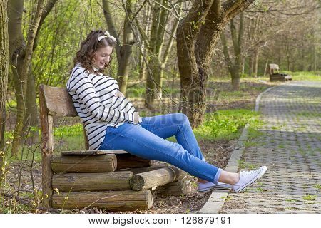 Beautiful pregnant woman outdoor in the park on bench