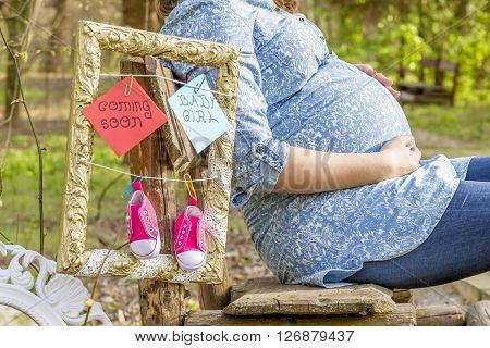 Pregnant woman outdoor in the park on bench with baby shoes.