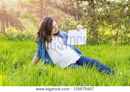 Beautiful pregnant woman outdoor with a paper in hand showing the day birth of her baby.