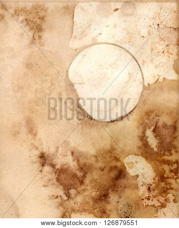 An abstract old paper texture: a sheet of paper toned and painted to look like old parchment with a ring from a coffee or tea cup with a place for text or logo
