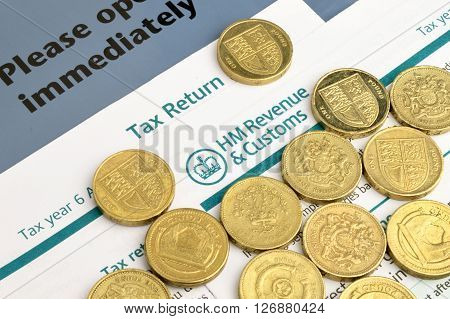 A close up of HM paper tax return with coins.