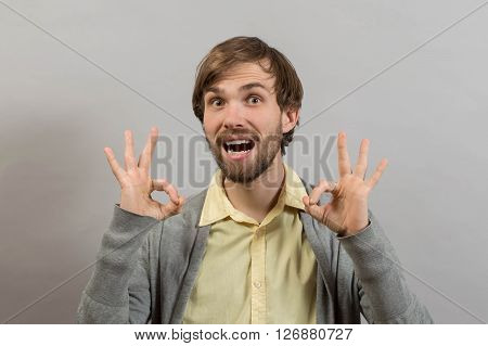 Everything is OK.Happy young man in shirt gesturing OK sign and smiling while standing against grey background