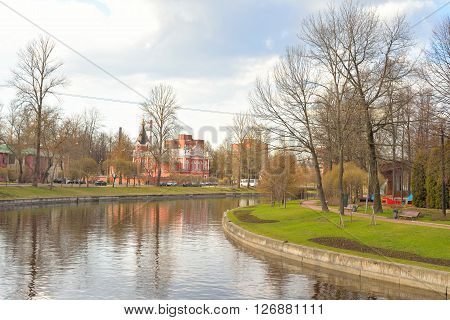 View Izhora River Church of the Ascension and City Garden in center of Kolpino town at spring sunny day on the outskirts of St. Petersburg Russia.