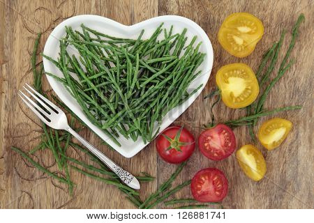 Diet health food of samphire and tomato vegetables on a heart shaped china plate with silver fork and loose over old wood background.