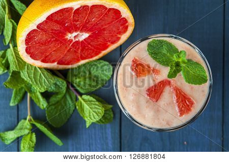 Glass of homemade smoothie with grapefruit banana and mint leaves . Conception of healthy food. Nonalcoholic drinks.