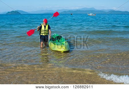 man carrying kayak paddle on shoulder at sea beach