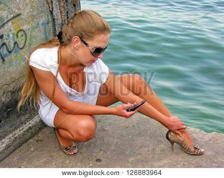 young pretty woman sitting alone on the pier near the sea and sending message on mobile