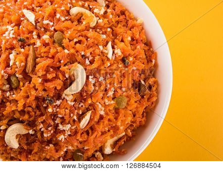 tasty gajar halwa or gajar ka halwa made up or fresh carrot, sugar and milk. decorated with almond or badam, cashewnuts and pistachios, favourite north indian dessert usually served in weddings