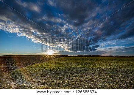 Sunstar on the horizon on blue sky with ominous clouds over a field with rests of snow