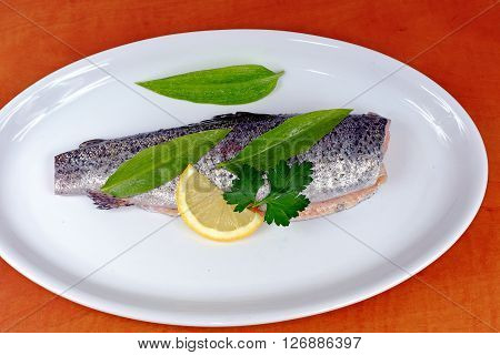 Trout with wild garlic lovage and lemon on a white plate prepared for roasting or grilling