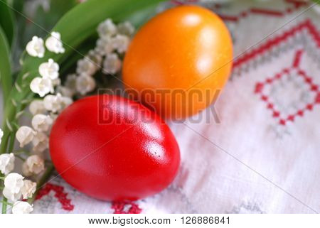 two red and orange easter eggs with may-lily flowers