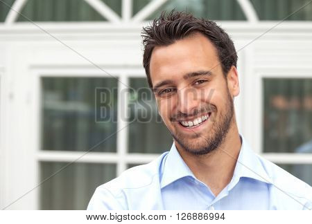 Latin business man smiling outdoors in front of his office