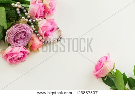 Styled desktop scene  with pink flowers, copy space on white table