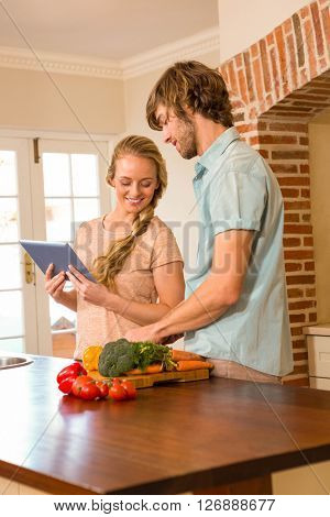 Cute couple cooking and using tablet in the kitchen
