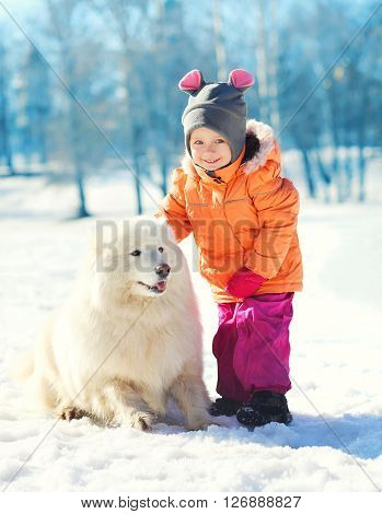 Cheerful Child With White Samoyed Dog On Snow In Winter Park