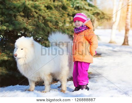 Little Child With White Samoyed Dog On Snow In Winter Day