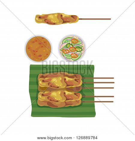 Satay on banana leaves and bowl with dipping sauce.