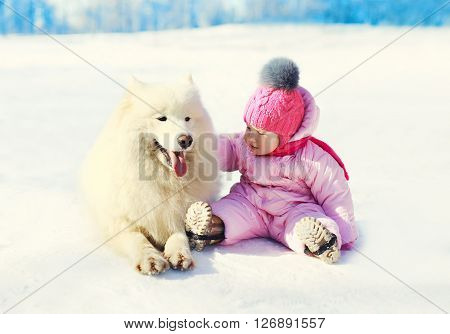 Child with white Samoyed dog sitting on snow in winter day
