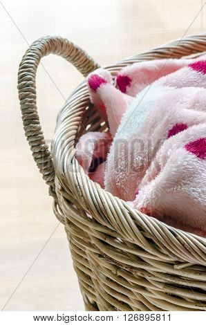 Close up of rattan basket with pink blanket.