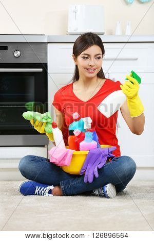 Beautiful woman in protective gloves with different cleaning sprays