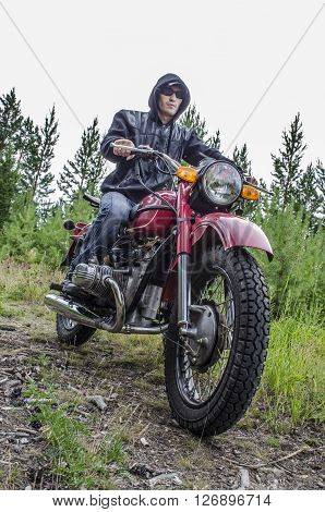 Cool, young biker rides in the forest on a powerful motorcycle.