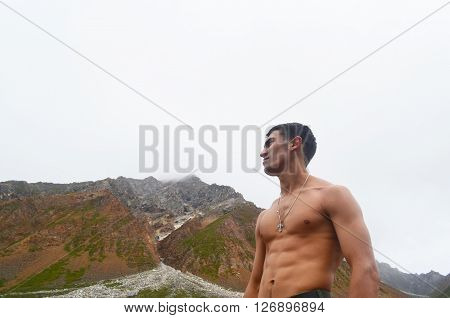 Brutal man looks at the top of the mountain.