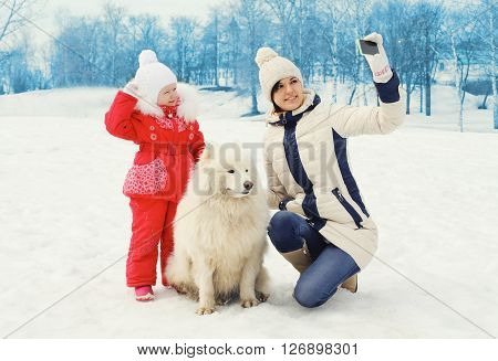 Mother And Child With White Samoyed Dog Makes Selfie Portrait On Smartphone In Winter Day