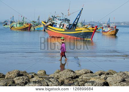 MUI NE, VIETNAM - DECEMBER 25, 2015: Vietnamese woman walking on the coastal strip on the background of fishing boats. The fishing harbour of Mui Ne, Vietnam