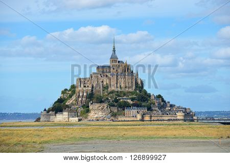 View Of Mont Saint Michel, France, With A Green Field And Sea
