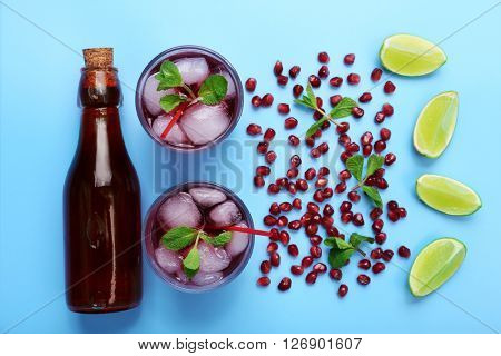 Pomegranate drink with lemon and ice cubes on blue background, top view