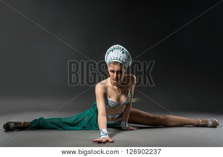 Charming go-go dancer posing while doing gymnastic split