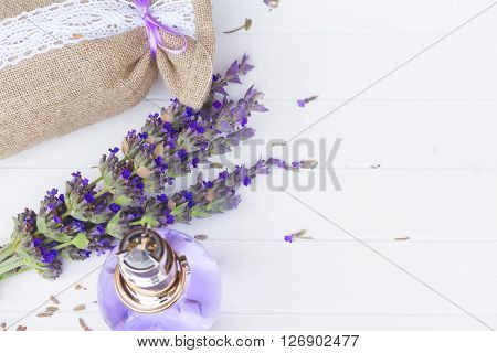 Lavender herbal water in a glass bottle with fresh and dry flowers in pouch, copy space on white wooden table