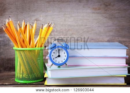 Set of pencils in metal holder, stack of books and alarm clock on wooden background
