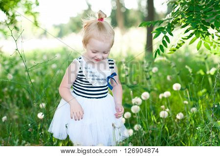 Funny little girl 2-3 year old playing outdoors. Wearing stylish striped dress. Walking in meadow. Childhood.