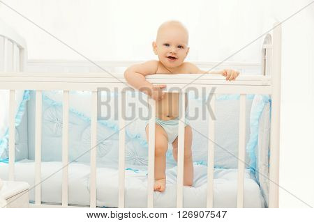 Little Baby Standing On The Bed At Home In Room