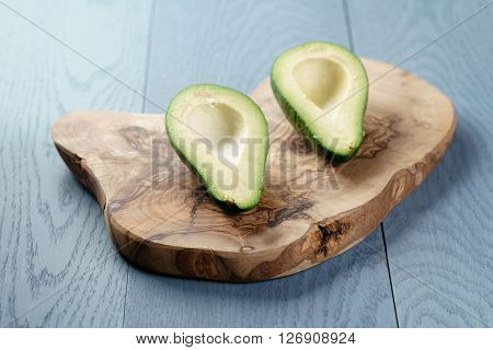 sliced ripe avocados on olive cutting board, shallow focus