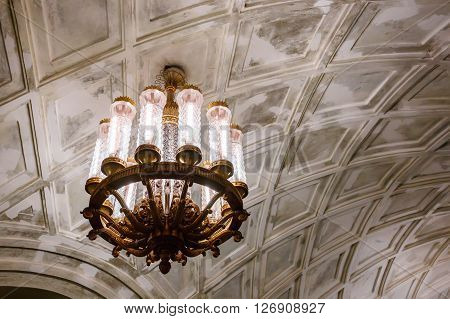 MOSCOW - MARCH 3: Chandelier in Prospekt Mira metro station on March 3 2016 in Moscow. The ceiling vault is decorated with casts and lighting comes from several cylindrical chandeliers.