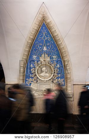 Maiolica panel with blurred in motion people at the foreground in the Taganskaya metro station in Moscow Russia.