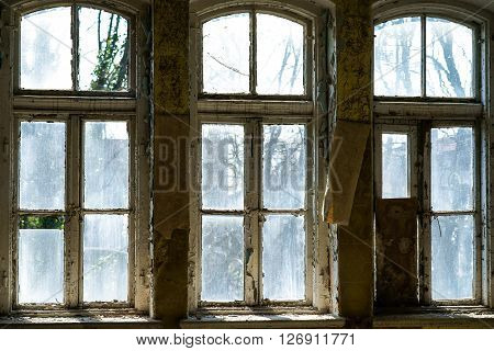 Old broken white painted windows frames with broken glasses