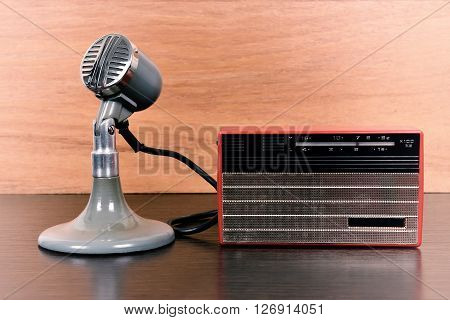 Red vintage radio and retro microphone on wooden table. Vintage effect