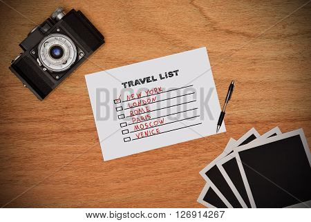 Camera and paper with drawing travel list. Work desk tourist.